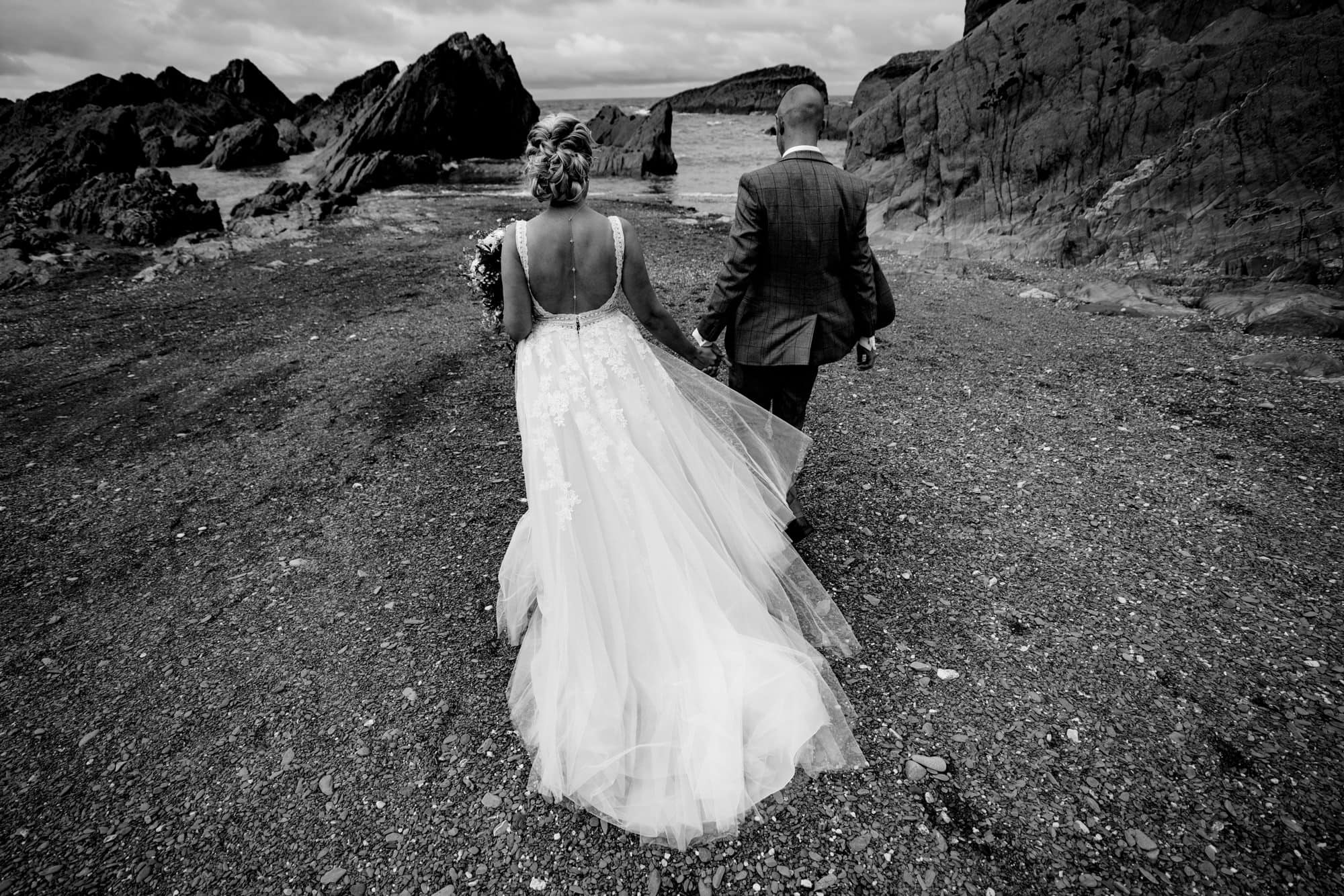 black and white image of wedding couple running towards the beach at tunnels beaches wedding venue