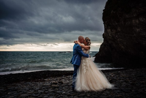 Wedding couple on stormy beach cliffs and wind