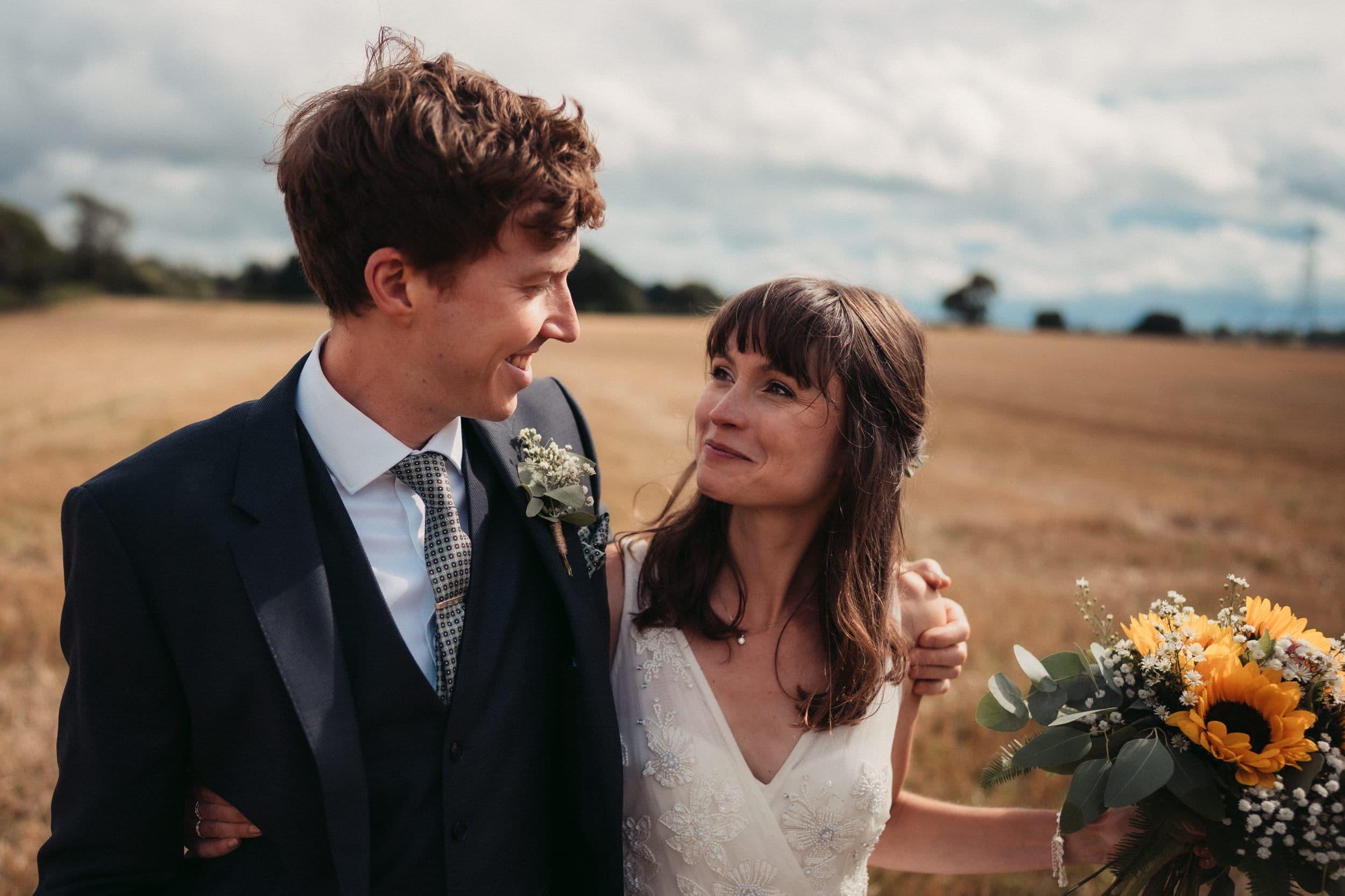married couple in freshly cut wheat field