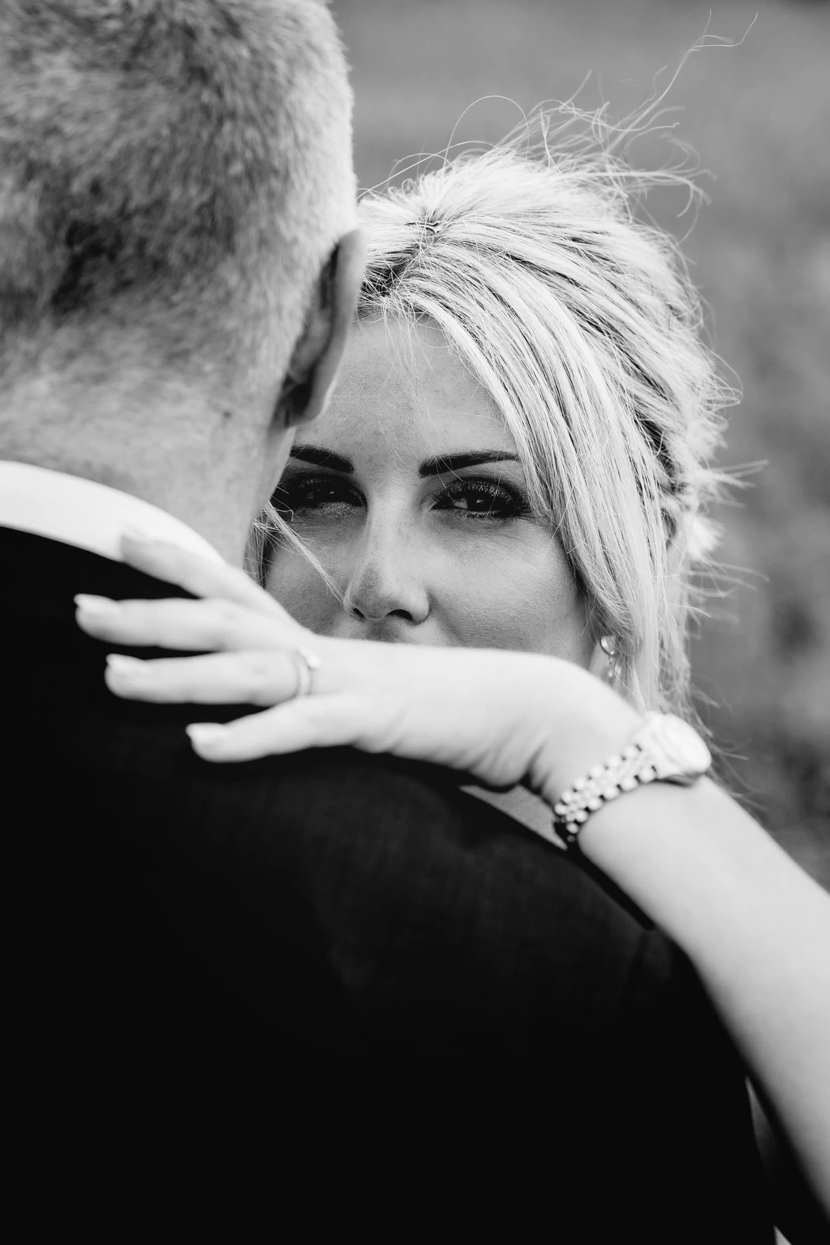 bride looking over the shoulder of her husband