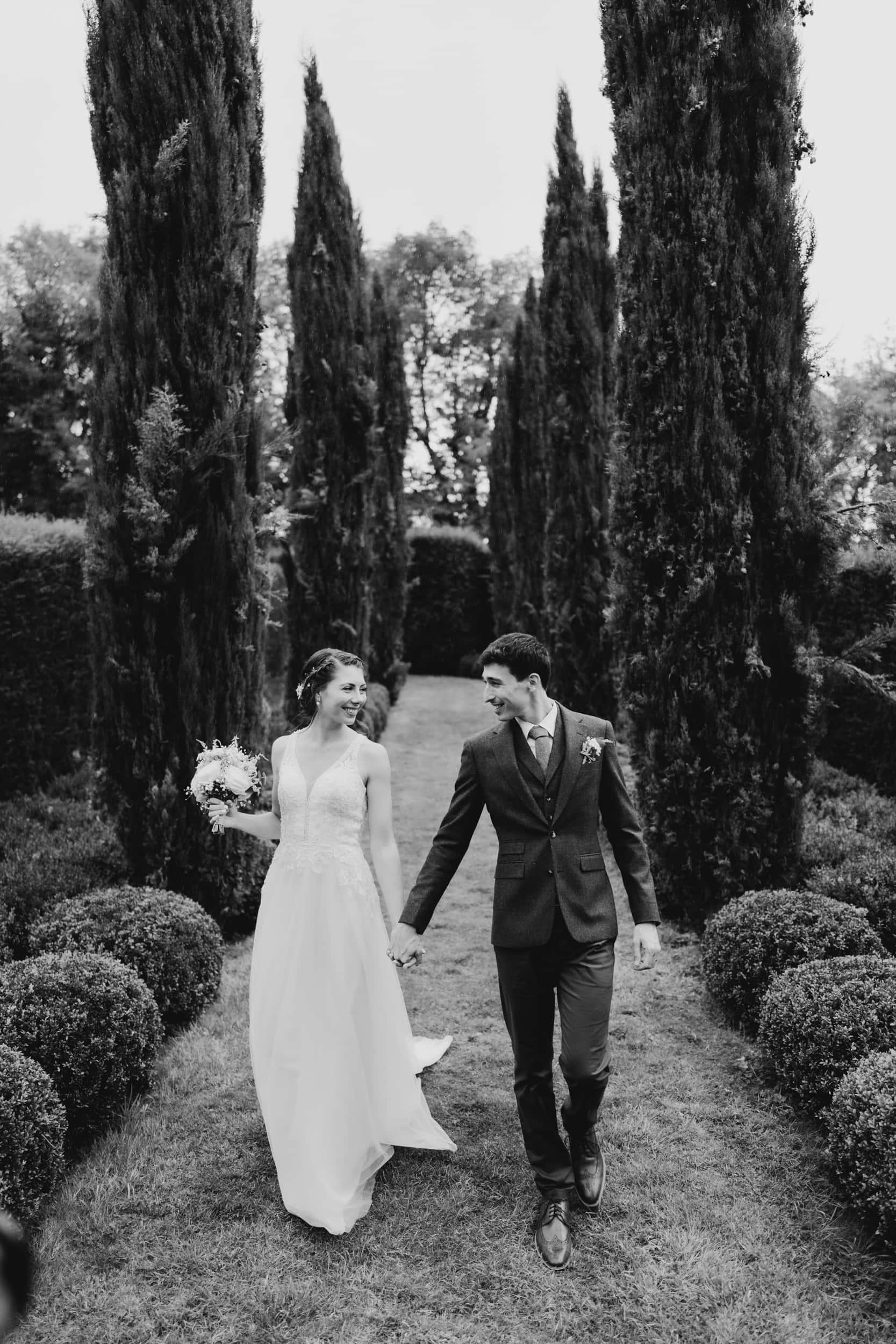 couple walking through garden on wedding day