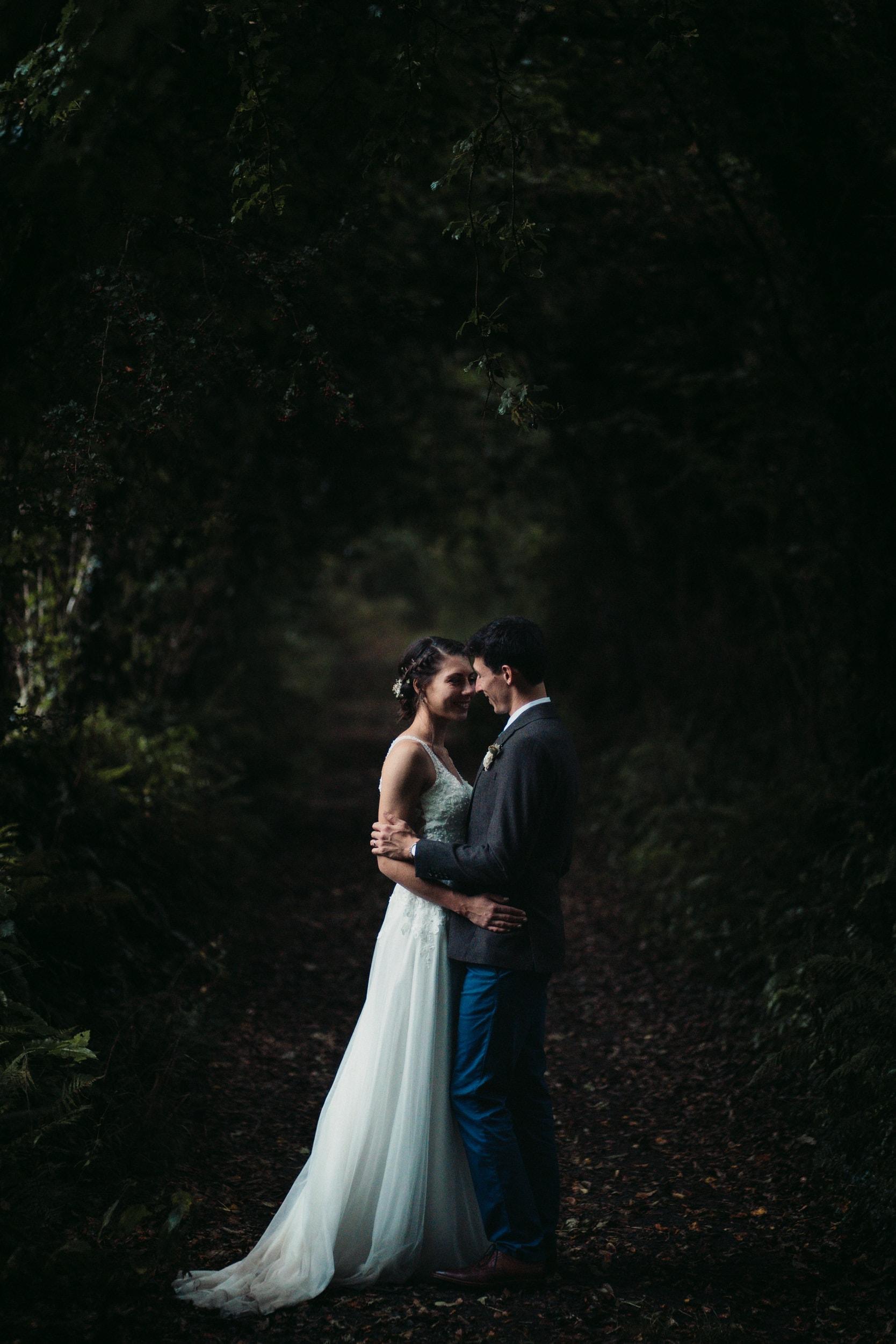 bride and groom in wooded alleyway