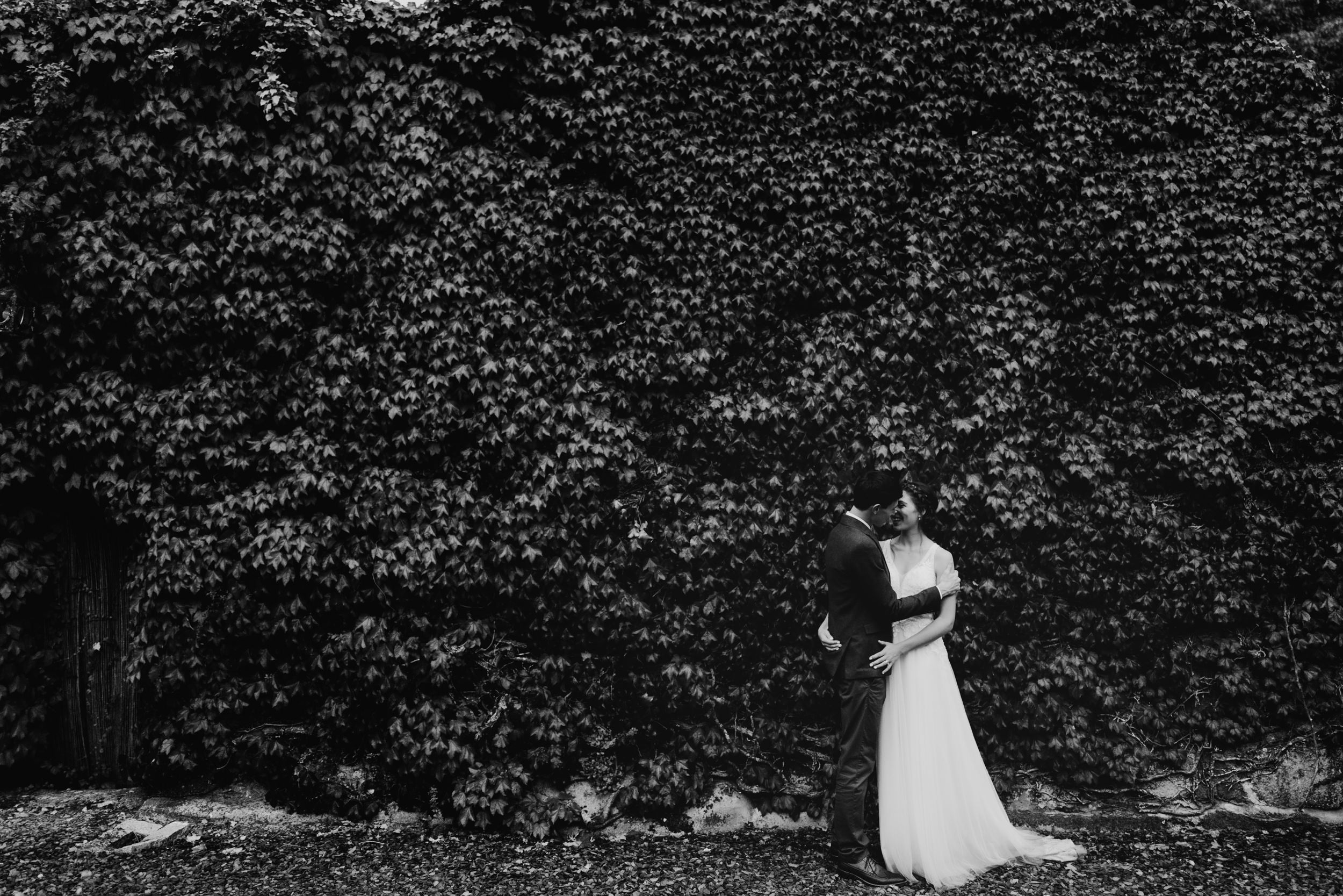 bride and groom stood in front of ivy wall
