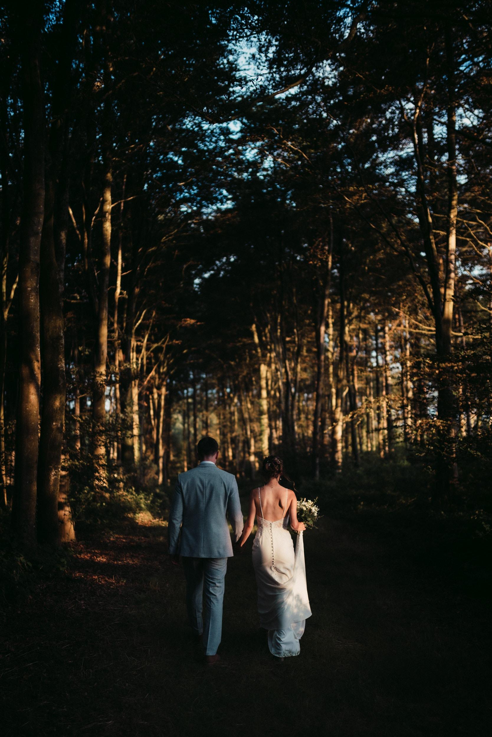 married couple walking down a treeline in evening sun