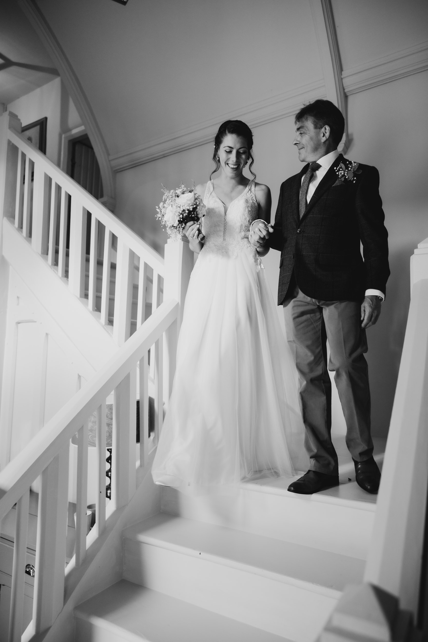 father and bride walking down stairs