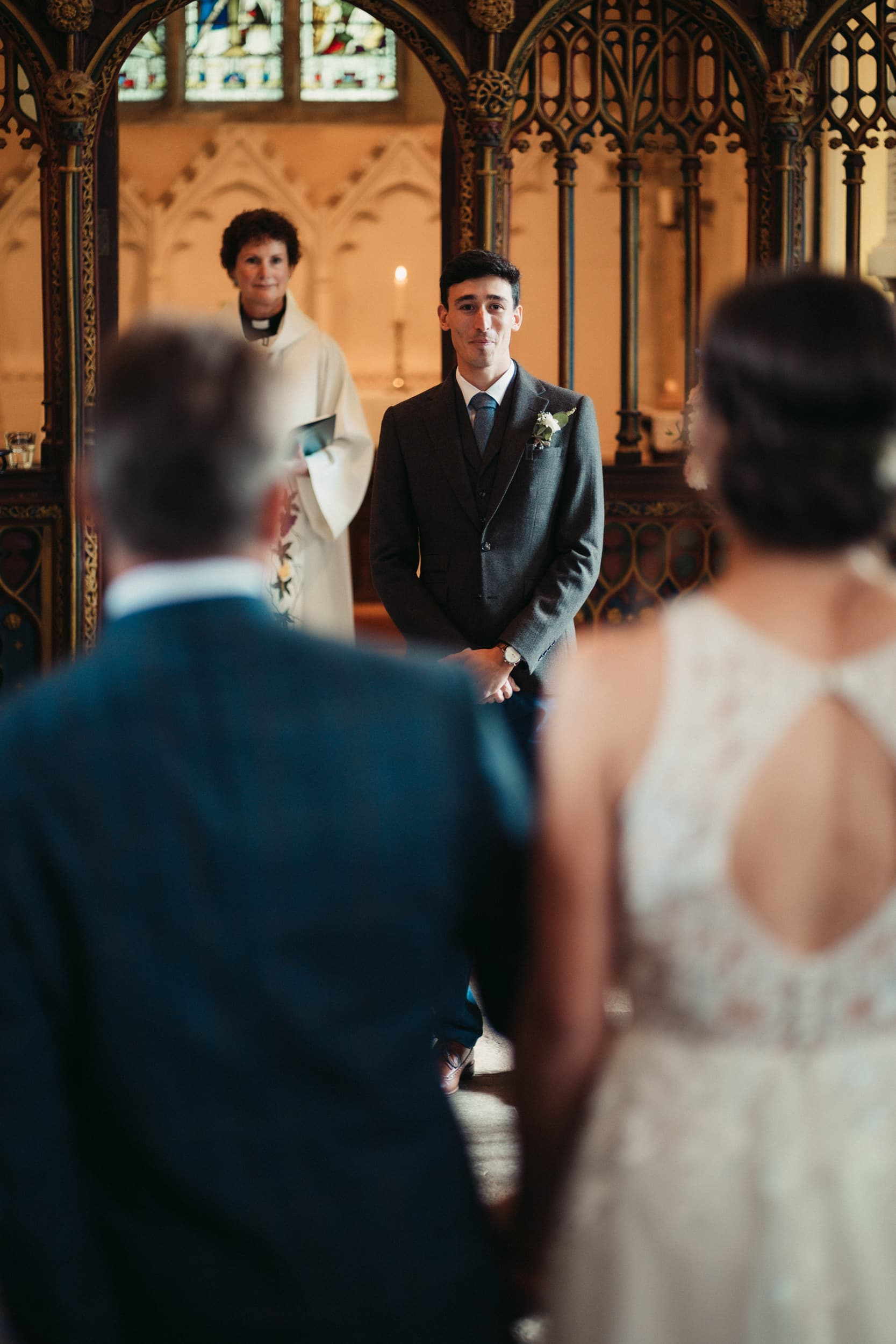 groom watching bride to be walking down the aisle towards him