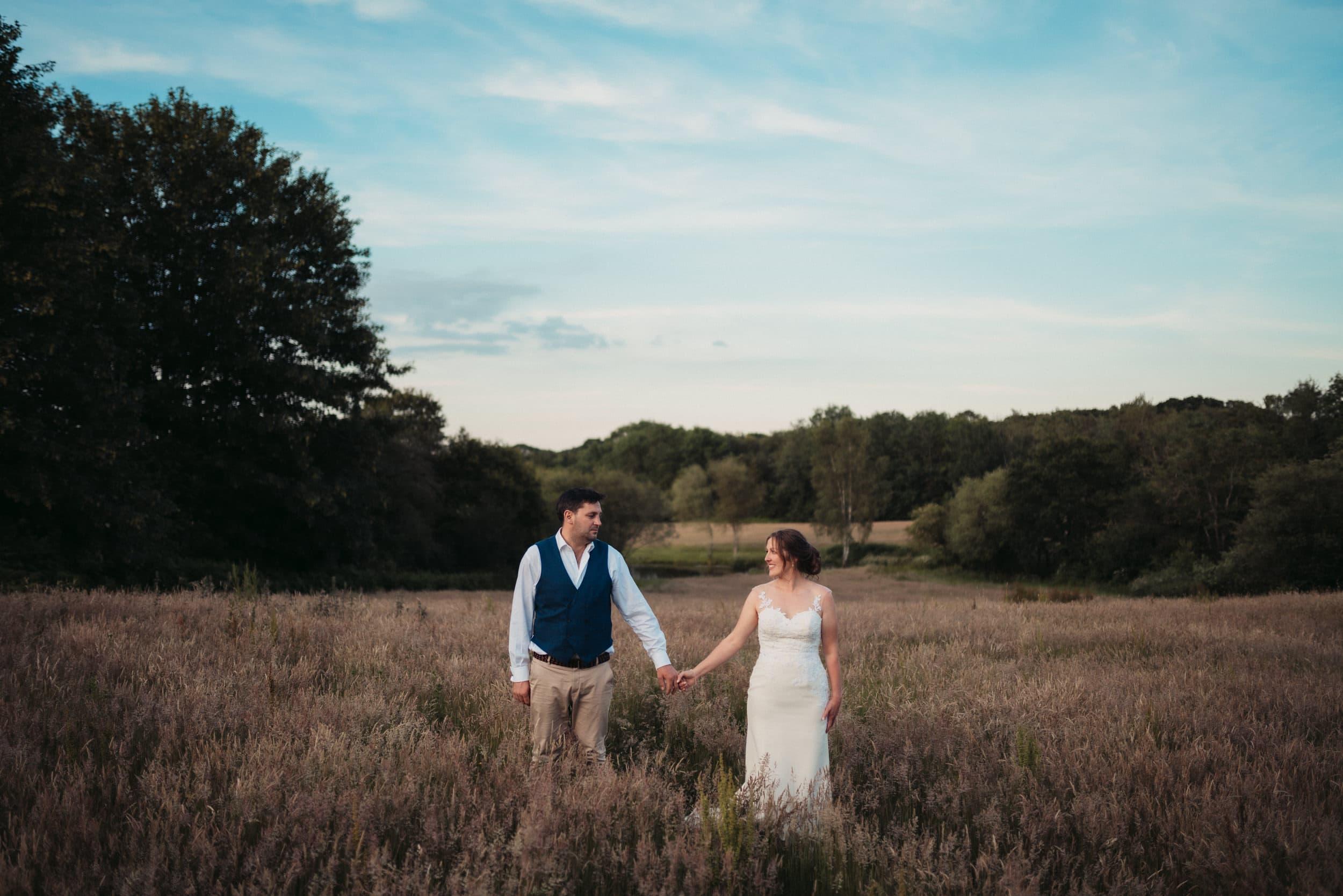 married couple posing in long grass field