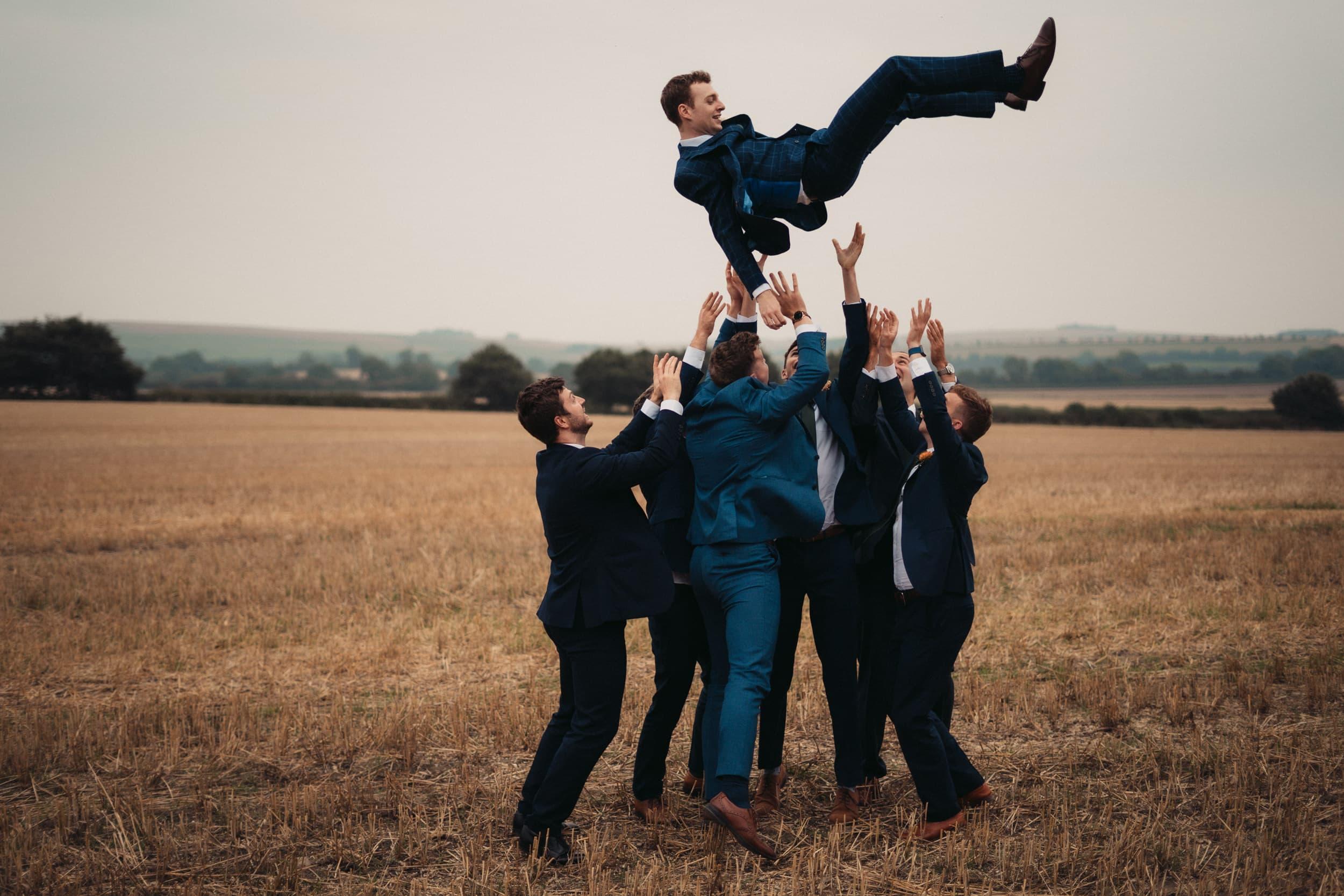 groom being thrown in air by best men