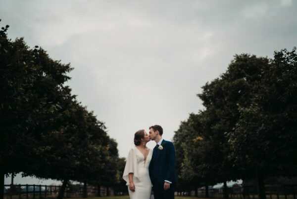 married couple kissing on driveway to rye hill barn