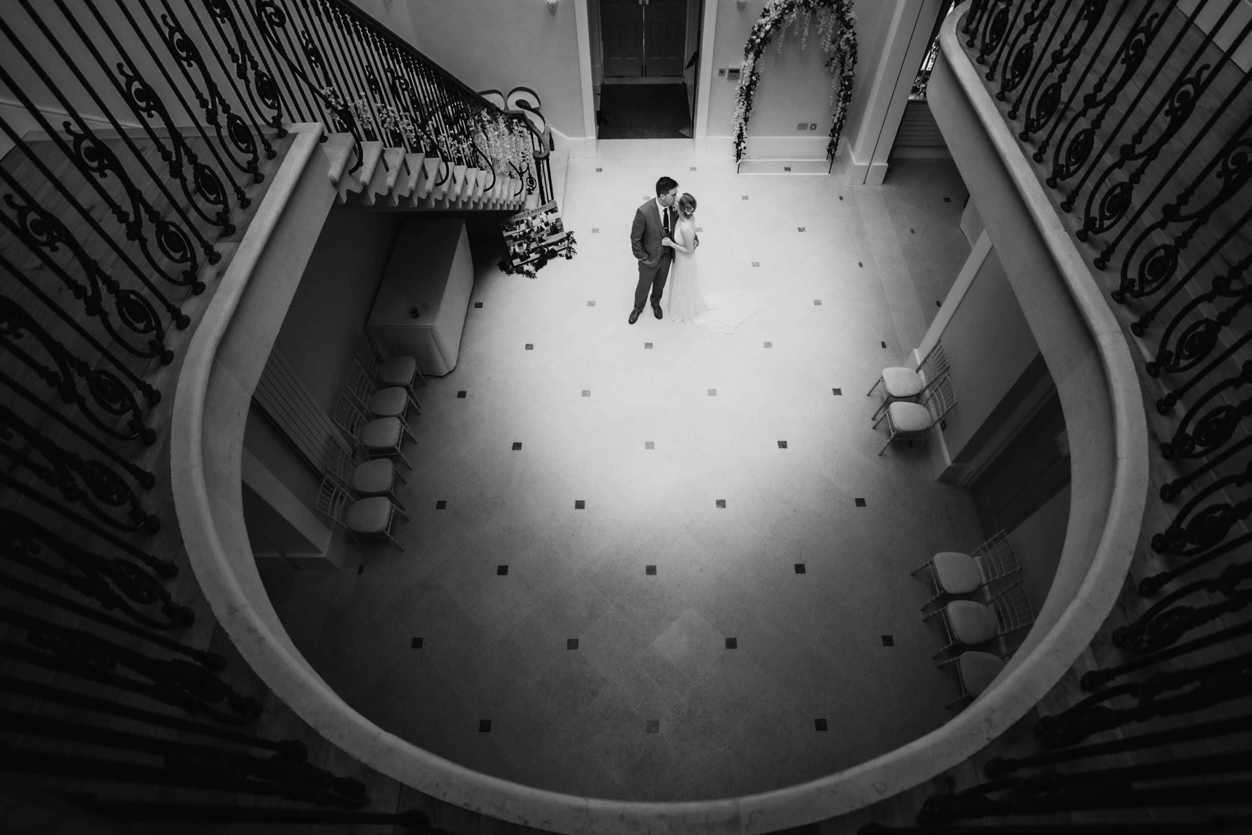 bride and groom standing in elaborate atrium